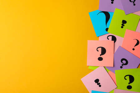 Paper cards with question marks on yellow background, flat lay. Space for text 写真素材