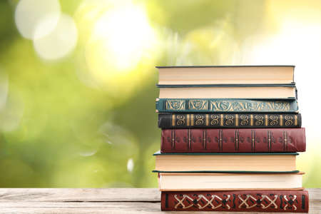 Collection of different books on wooden table against blurred green background, space for text