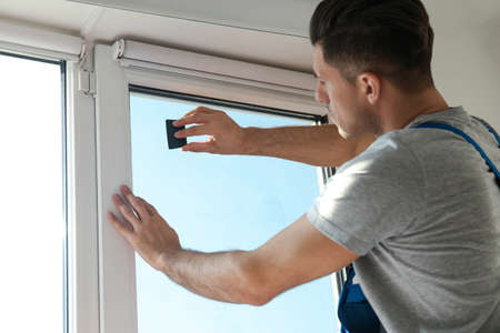Professional worker tinting window with foil indoors