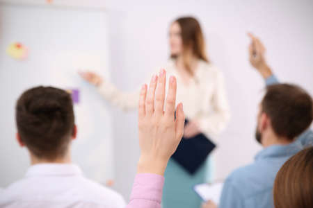 Woman raising hand to ask question at business training indoors, closeup
