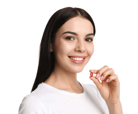 Young woman with vitamin capsule on white background Stock Photo
