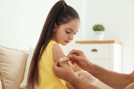 Father putting sticking plaster onto daughter's arm at home