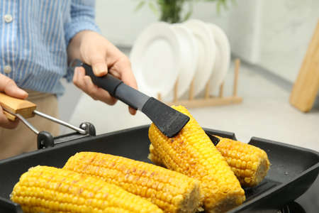 Woman taking corn from grill pan with tongs in kitchen, closeup