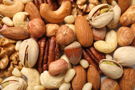 Different delicious nuts as background, closeup view