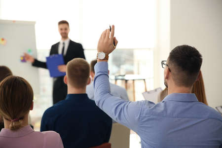Man raising hand to ask question at business training indoors Stock Photo