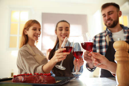 Happy people drinking wine while cooking food in kitchen Stock Photo