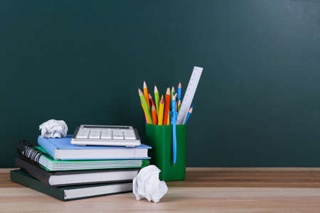Set of stationery and crumpled paper on wooden table near chalkboard. Doing homework