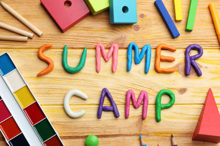 Flat lay composition with phrase SUMMER CAMP made of modelling clay on wooden background Archivio Fotografico