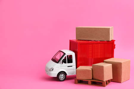 Truck model and carton boxes on pink background, space for text. Courier service