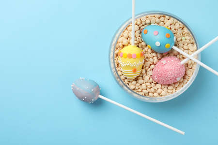 Egg shaped cake pops for Easter celebration on light blue background, flat lay