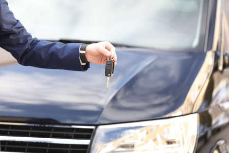 Man holding key in modern auto dealership, closeup. Buying new car