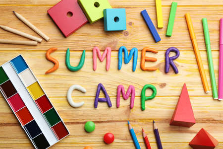 Flat lay composition with phrase SUMMER CAMP made of modelling clay on wooden background Stock fotó