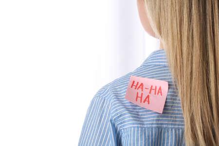 Woman with HA-HA-HA sticker on back against light background, closeup. April Fool's Day Banco de Imagens