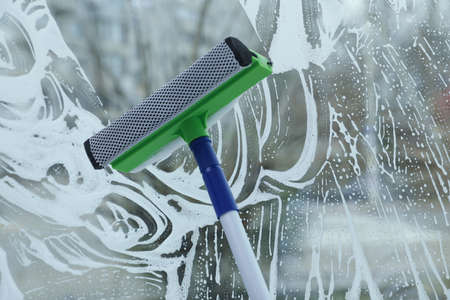 Cleaning window with squeegee indoors. Household chores