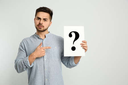 Confused man holding question mark sign on light background