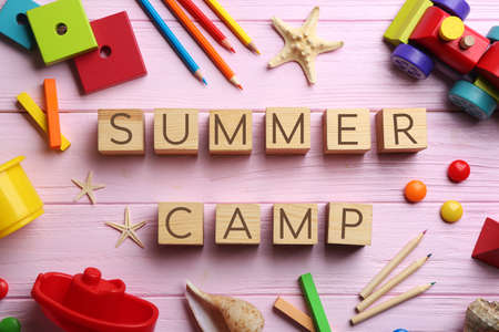Flat lay composition with phrase SUMMER CAMP made of cubes on pink wooden background