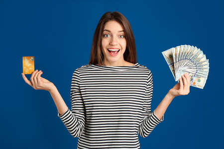 Excited young woman with cash money and credit card on blue background