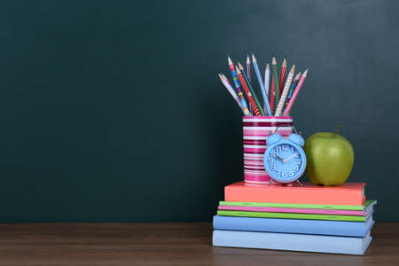 Composition with stationery, apple and alarm clock on table near chalkboard, space for text. Doing homework