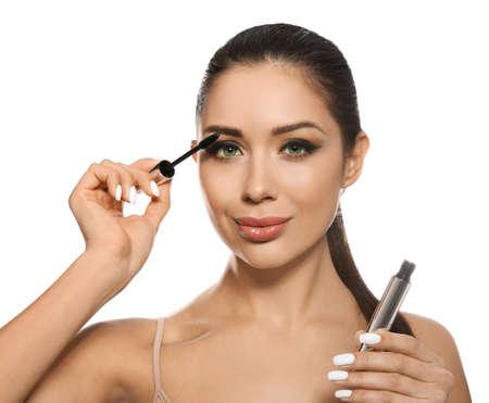 Beautiful woman applying mascara on white background. Stylish makeup