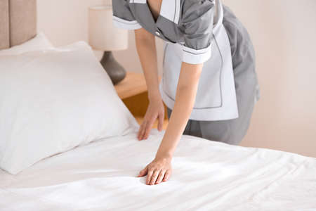 Young chambermaid making bed in hotel room, closeup