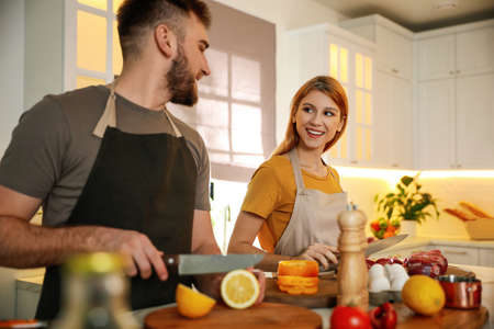 Happy people cooking food together in kitchen
