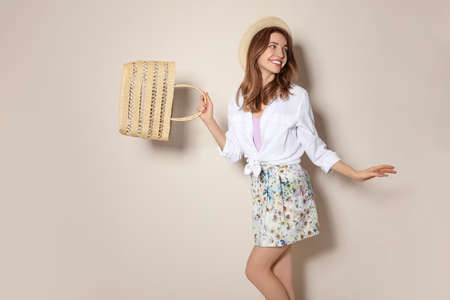 Young woman wearing floral print skirt with straw bag on beige background