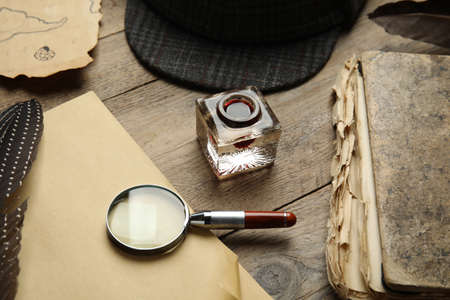 Composition with different vintage items on wooden table. Detective's workplace