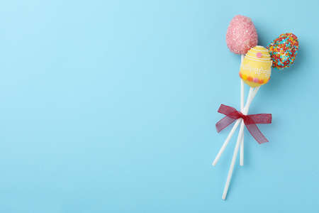 Egg shaped cake pops and space for text on light blue background, top view. Easter celebration