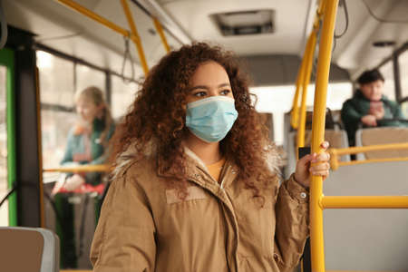 African-American woman with disposable mask on bus. Virus protection Imagens