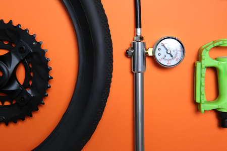 Set of different bicycle parts and manometer on orange background, flat lay