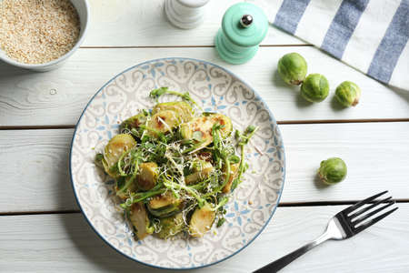 Delicious salad with roasted Brussels sprouts on white wooden table, flat lay