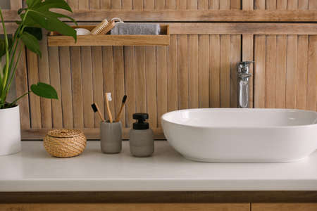 Toiletries and stylish vessel sink near wooden wall in modern bathroom