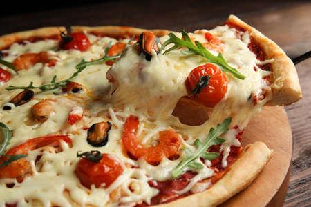 Delicious seafood pizza on wooden board, closeup Foto de archivo