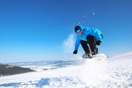 Man snowboarding on snowy hill, space for text. Winter vacation