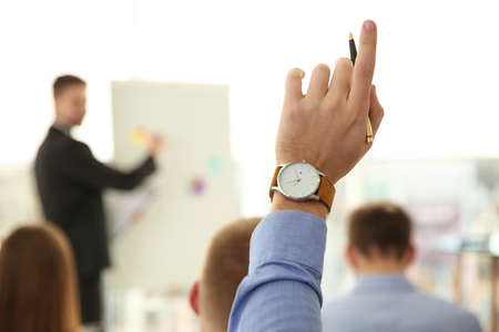 Man raising hand to ask question at business training indoors, closeup Фото со стока