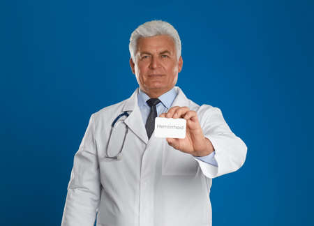 Doctor holding business card with word HEMORRHOID on blue background