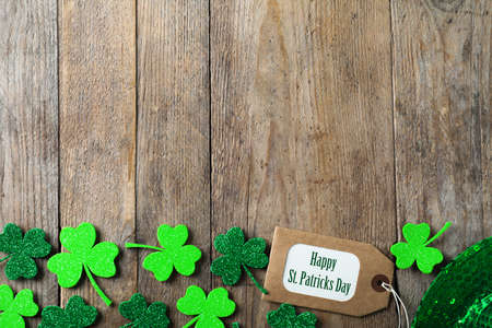 Clover leaves, tag and space for text on wooden table, flat lay. St. Patrick's Day celebration