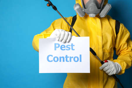 Man wearing protective suit with insecticide sprayer holding sign PEST CONTROL on blue background, closeup