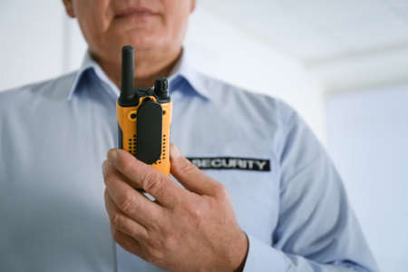 Professional security guard with portable radio set indoors, closeup
