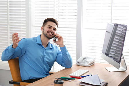 Lazy employee talking on smartphone at table in office Фото со стока