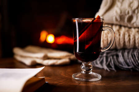 Tasty mulled wine, book, knitwear and blurred fireplace on background