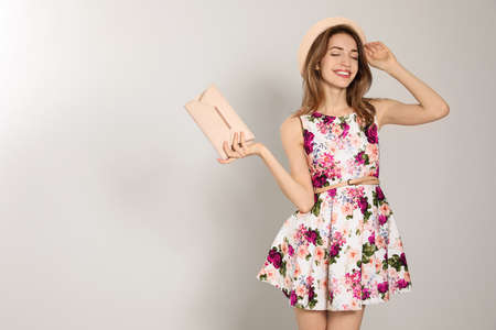 Young woman wearing floral print dress with clutch purse on light background. Space for text