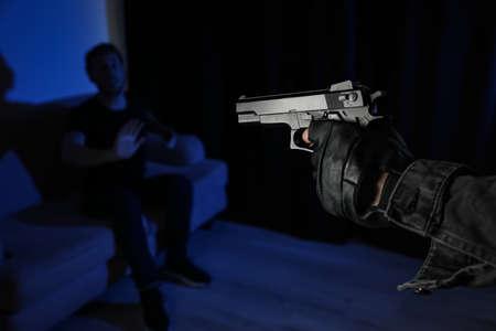 Man aiming his victim with gun in dark room, closeup. Dangerous criminal