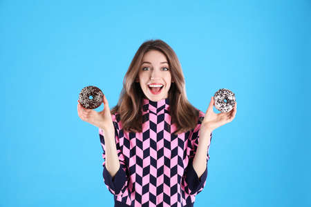 Beautiful young woman with donuts on light blue background 免版税图像