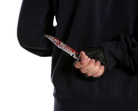 Man with bloody knife behind his back on white background, closeup. Dangerous criminal