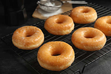 Sweet delicious glazed donuts on black table Foto de archivo