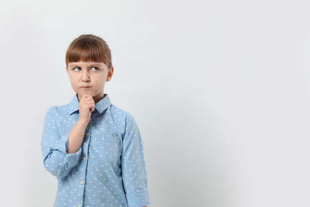 Pensive little girl on white background, space for text. Thinking about answer to question 免版税图像