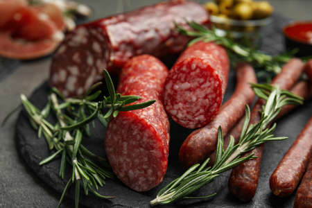 Different types of sausages served on grey table, closeup Фото со стока