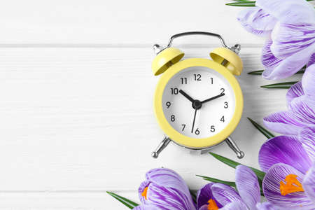 Yellow alarm clock, spring flowers and space for text on white wooden table, flat lay. Time change Stock Photo