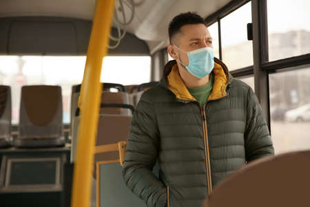 Man with disposable mask on bus. Virus protection